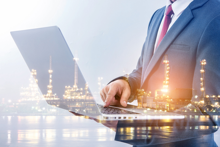 Double exposure of businessman using laptop with oil and gas refinery background. Industrial invested concept