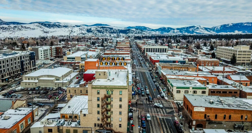 Aerial View of Main Street in downtown Bozeman Montana. Winter snow is scattered on streets and buildings with the mountain range covered in snow in the distance. Famous Baxter Hotel Sign is seen up close.